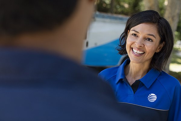 woman in at&t uniform smiling while talking with client