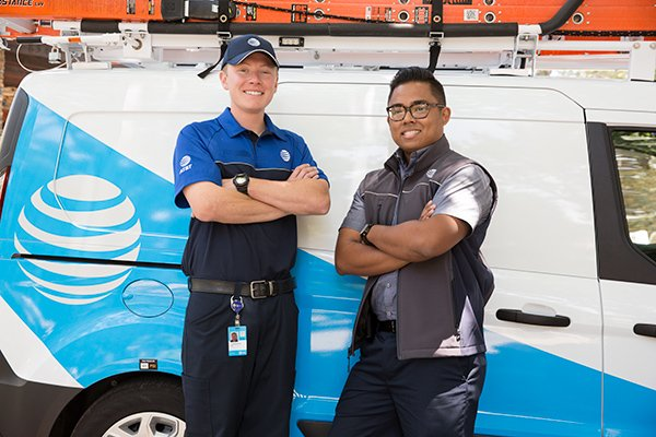 two at&t technicians standing in front of service van with arms crossed and smiling
